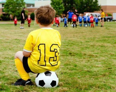 遠くからサッカーを見つめる少年